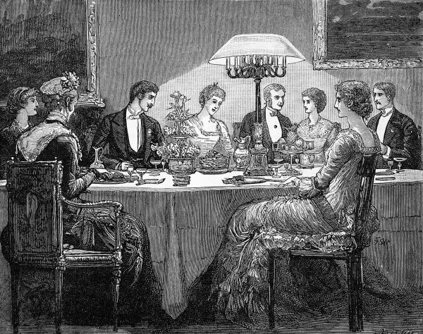 A dinner scene from 1881 showing ladies and gentlemen around a table dressed in evening attire. The table is lit by a large lamp and as well as the dinner plates, there are floral and fruit centrepieces