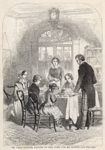 A Victorian family saying grace at the dinner table