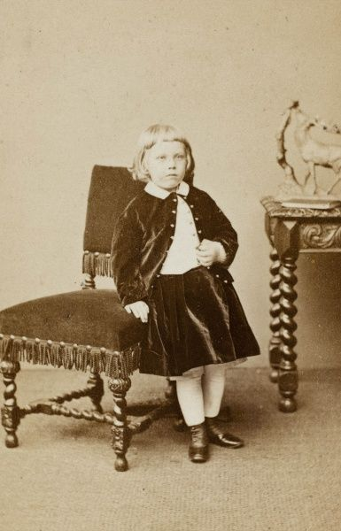 A little Victorian girl wearing a matching velvet jacket and skirt, leaning against an upholstered chair in the photographer's studio