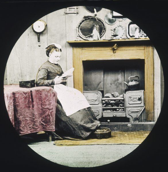 A woman sits reading by the kitchen range
