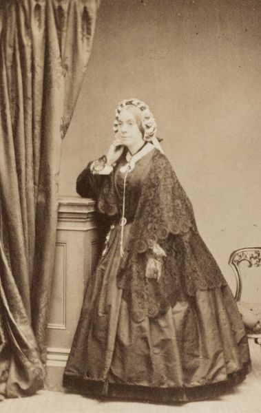 A middle-aged Victorian woman in a dark crinoline dress with a lacy shawl