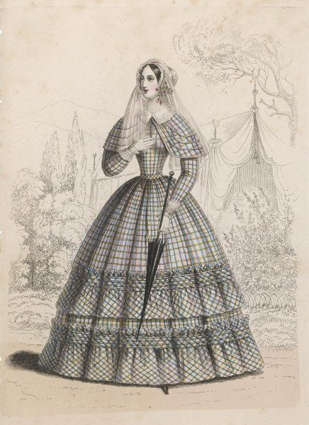 A Viennese woman wears a dress & a small cape in a large checked print. The cuffs & collar are of lace. A long veil falls from the back of her bonnet
