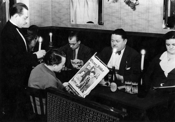 Owing to the high price of electricity in Vienna, Austria, consumers have gone 'on stike', dining out in restaurants with candles burning from bottles! Date: 1933