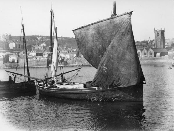 A view of fishing boats in the bay at St Ives, Cornwall, with the town in the background