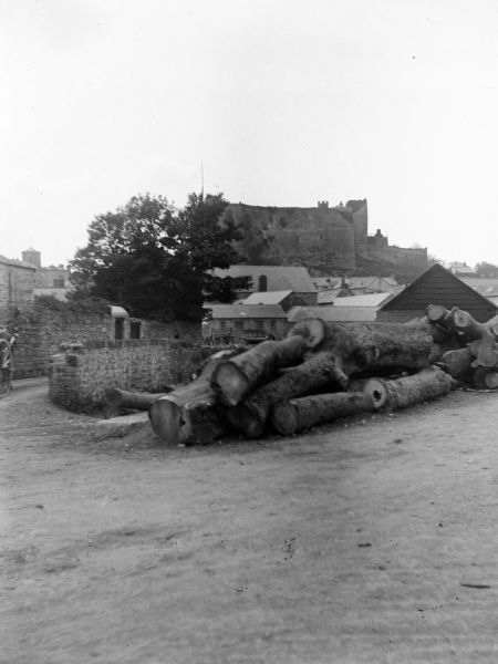 A distant view of the Castle from Old Bridge Street, Haverfordwest, Pembrokeshire, Dyfed, South Wales, with a pile of timber in the foreground