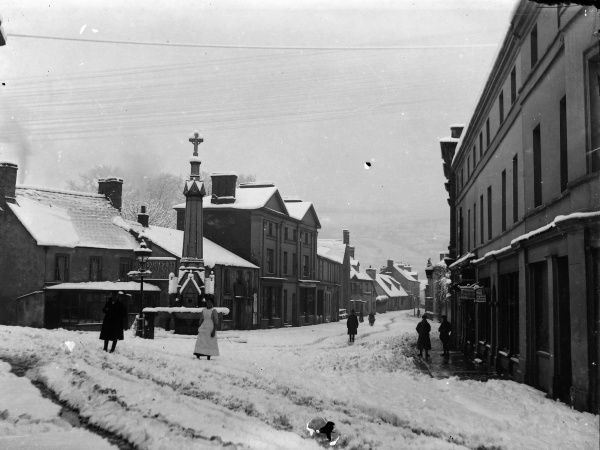 A view down the High Street from the Bear Hotel, in the town centre, Crickhowell, Powys, Mid Wales, with snow on the ground. Recently installed telegraph wires can be seen above