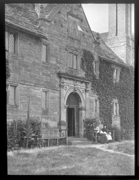 Exterior view of Sackville College, East Grinstead, West Sussex, a Jacobean almshouse founded in 1609 to provide sheltered accommodation for the elderly. Two elderly women can be seen sitting on a bench to the right of the doorway