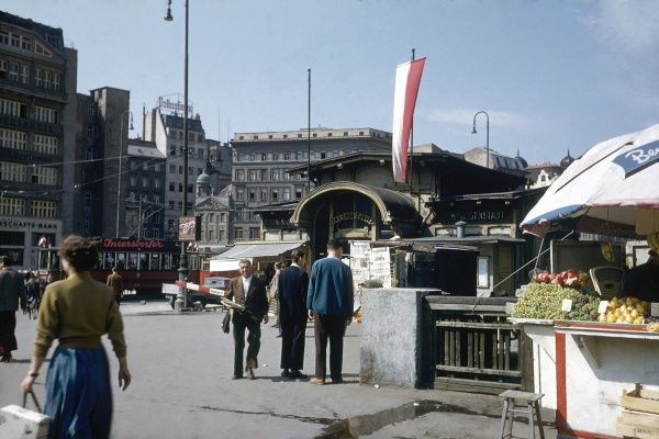 View of a market square, the Schwedenplatz, in Vienna, Austria. There is a stall on the right with fruit for sale, and a few people are out shopping. Date: 1953