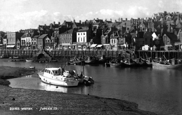 View of Whitby Harbour, North Yorkshire, with a long row of houses on the far side. Date: 1940s