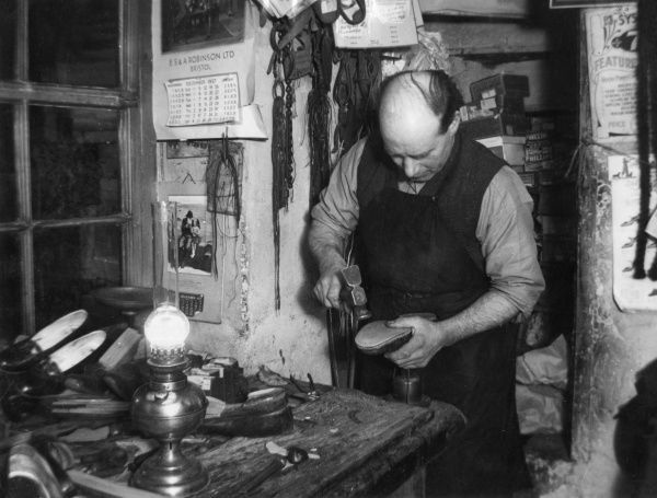 The village cobbler working by the light of his oil lamp in his workshop in Congresbury, Somerset, England