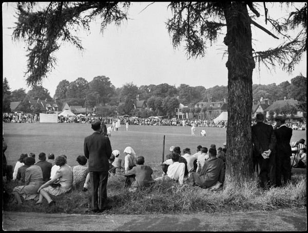 An enthusiastic crowd gather to watch a cricket match on the village green, Bearstead, Kent, England
