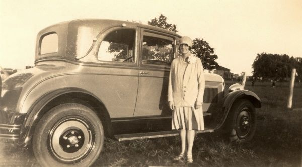 A lady dressed in the fashion of the day, stands next to her very fine vehicle. Date: 1920s