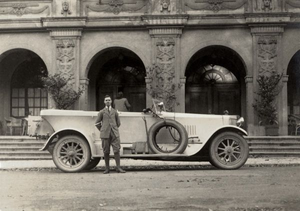 An enormous open-top saloon/sedan luxury car standing in front of an impressive arcaded facade/entrance to a large building. The owner of this impressive vehicle stands alongside in full tweed and plus-fours