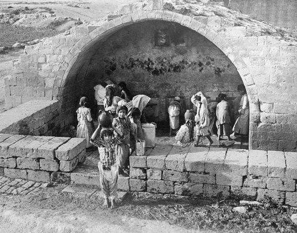 Children water carriers with jars on their heads at the Virgin's Well, Bethlehem. Date: early 1930s