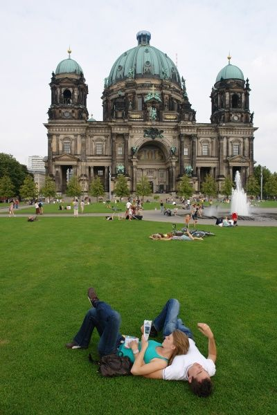 Visitors relax on the grass in front of Berlin Cathedral, Germany