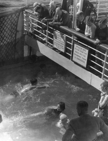 Passengers watching swimmers in the open air swimming pool of the 'Voltaire' luxury liner on its cruise to Norway. Date: 1930s
