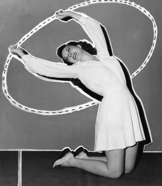 A young woman kneels down and swings her arms in the air, rotating her body to the left and then to the right. The aim of the exercise is a flat waist. Date: 1940s