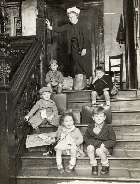 A matron who has temporarily looked after a group of young children watches over them as they sit on steps with their belongings packed, ready to be evacuated to the country