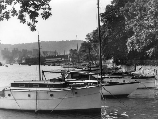 A glimpse of the esturay of the River Conway, north Wales, a peaceful anchorage for small craft, under the shadow of the grey walls of Conway Castle. Date: 1940s