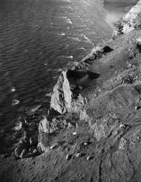 A glimpse of the precipitous cliffs, with grazing sheep, at Rhossili, on the Gower Peninsula, Glamorganshire, Wales. Date: 1960s