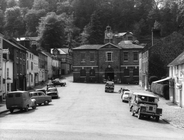 The Market Square at Montgomery, Montgomeryshire, Wales, set out on a hillside, with its Guildhall against a forest background. Date: 1960s