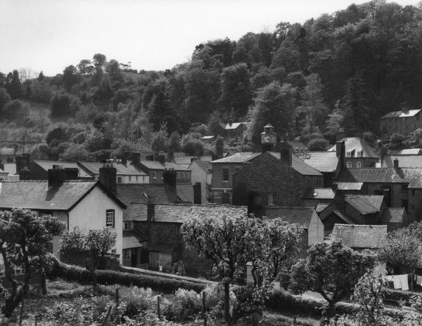 An impression of the town of Montgomery, Montgomeryshire, Wales, viewed from the churchyard, with the clock on the turret of the Guildhall rising above the rooftops. Date: 1960s