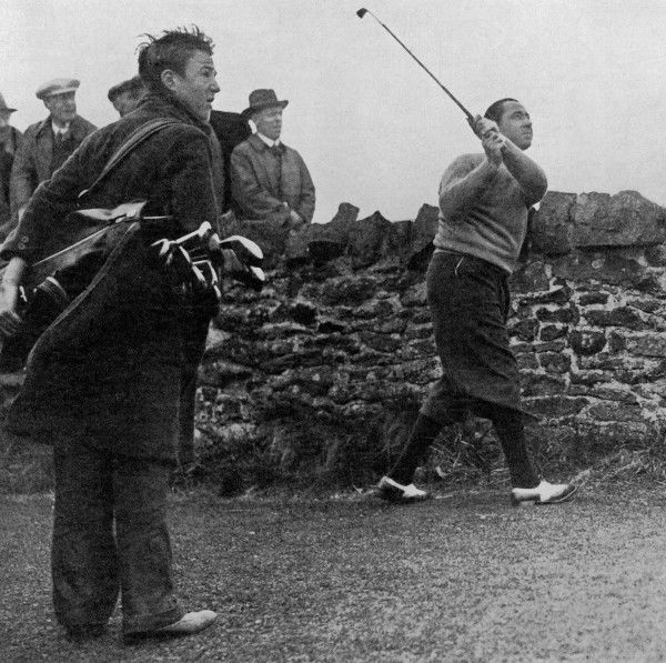 American golfer Walter Hagen plays a left handed shot from a difficult position on the ninth hole at Muirfield, Scotland, his ball too close to a stone wall to hit in his usual right handed manner. Hagen was playing the last day of The Open Championship