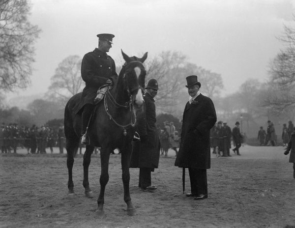 WALTER HENRY, 2ND BARON GILBEY OF ELSENHAM, ESSEX. Eldest son and heir of Sir Walter Gilbey the wine merchant and horse breeder. Chatting (in top hat) to a mounted policeman. Date: 1859 - 1945