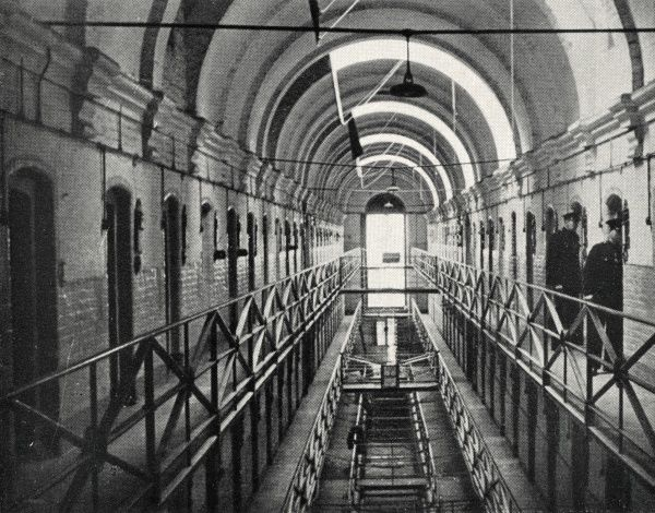 A galleried wing of Wandsworth Prison in south west London. Two warders inspect the cells