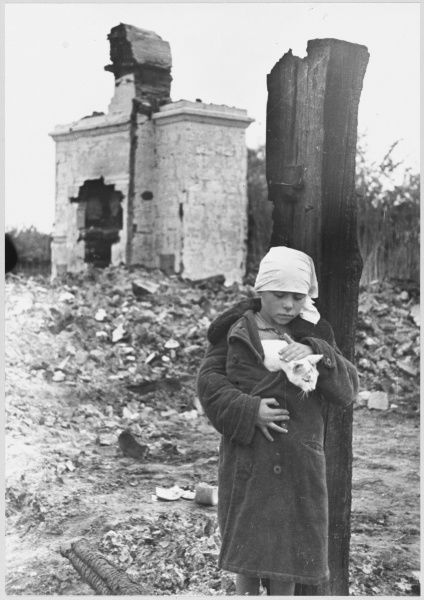 A Soviet war orphan walks through the ruins of a house with a cat tucked into her overcoat
