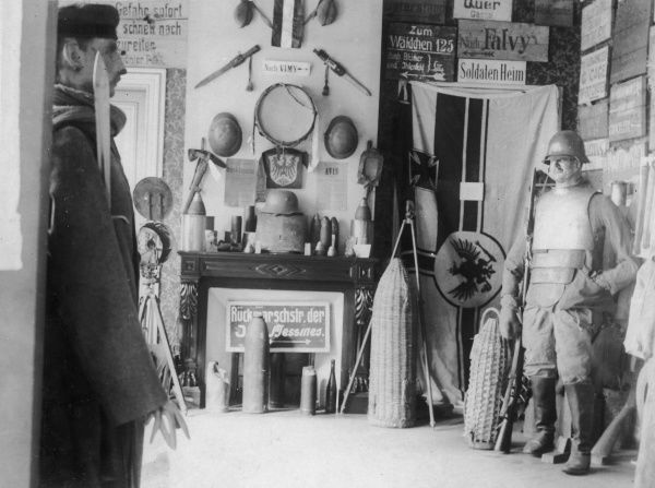 Part of an exhibition of German war trophies captured by the Allies during the First World War. Showing two dummies wearing German uniform, shells and wickerwork shell containers, various weapons, tin helmets and painted direction signs. Date
