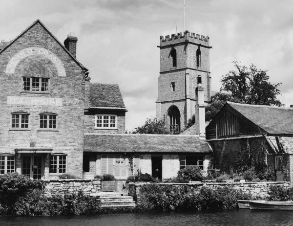 The Old Granary at Wareham, Dorset, converted into a Tea House, with St. Mary's Church behind and the River Frome in front