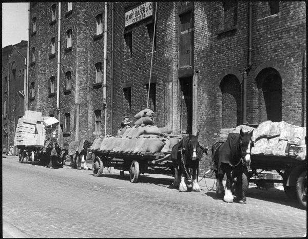 Stock is unloaded from horse- pulled wagons and drawn up into the warehouse by rope