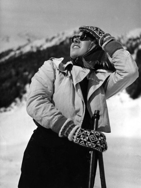 A model in warm, sensible ski- wear : Woollen gloves and a headscarf and sunglasses to protect her eyes from snow blindness! Date: 1930s