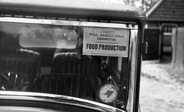 A wartime Food Production sticker of the County War Agricultural Committee in the windscreen of a car which drives the Committee to Lloyd George's farm at Churt, Surrey. Date: circa 1930s