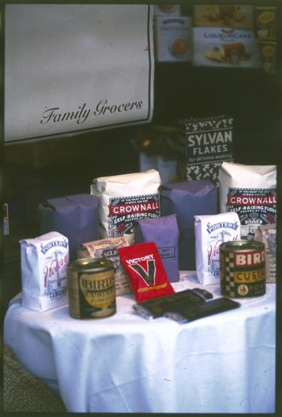 A table full of powdered and rationed goods, as available in Britain during World War Two, including 'Bird's Custard Powder', 'Victory V' lozenges and 'Sylvan Flakes&#39