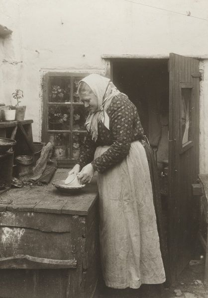 A woman in apron and scarf washing up a mug and plate outside her home, 1910. Date: 1910
