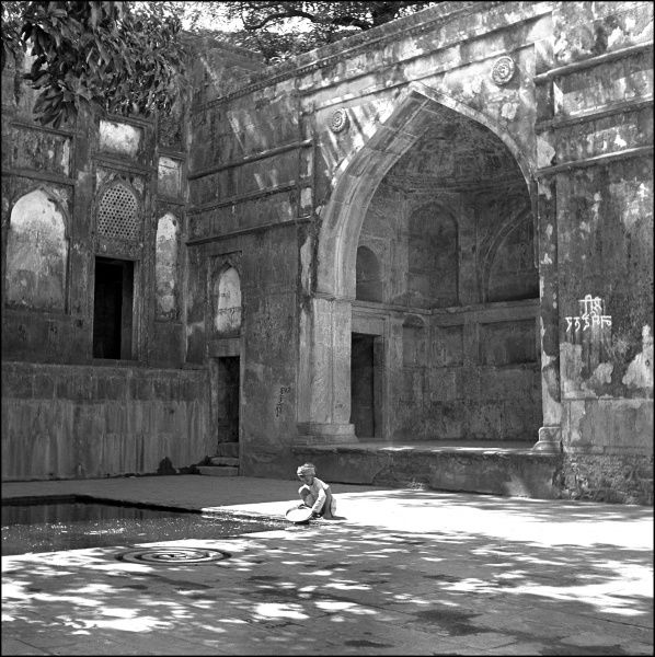 A young boy washes a large platter in a courtyard pool of a desertd Palace building in Mandu, Madhya Pradesh Province, India. Photograph by Ralph Ponsonby Watts