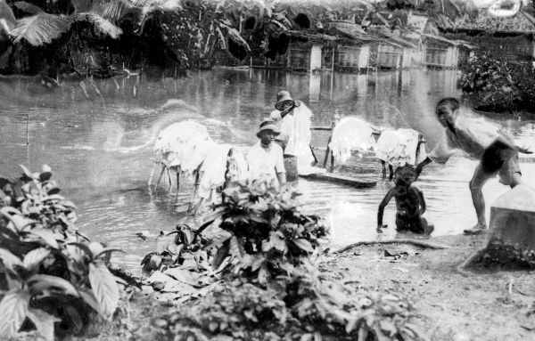 Washing day in Java, Dutch East Indies. The laundry man collects the dirty linen and carries it in a curiously constructed bamboo yoke into a shallow part of the river. Date: 1930s