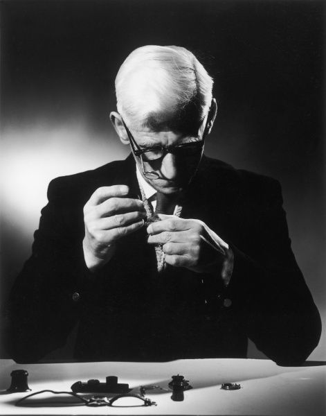 A suited man concentrates very hard as he fixes a wrist watch