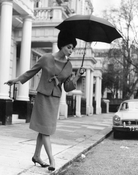 A smart young woman who can step off a pavement and hold an umbrella simultaneously! Date: 1960s