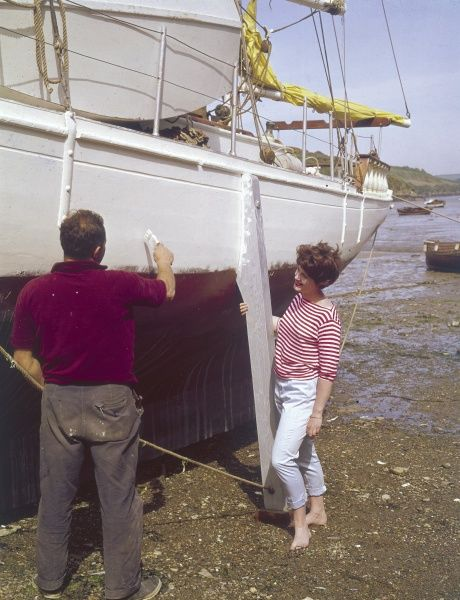 A man gives his boat a fresh coat of paint, while a young woman literally watches the paint dry! Date: 1965