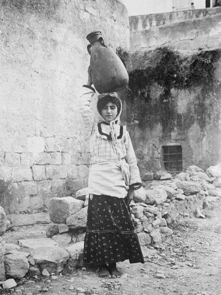 A little girl water carrier with the water jar on her head, Palestine. Date: early 1930s