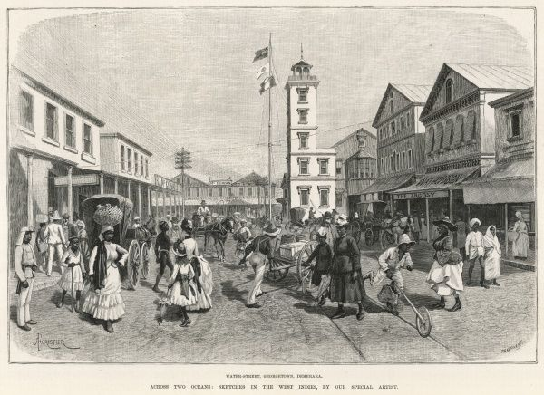 A busy street scene in Georgetown, Demerara, a region of Guyana showing various nationalities going about their business, pushing carts, driving horses, and carrying goods on their head against a backdrop of shops and businesses
