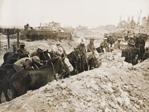 British troops and horses at a watering point in a ruined village on the Western Front in France during the First World War. Date: 1914-1918