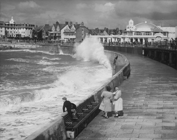 A young boy defies the waves at Porthcawl, Glamorgan, Wales. His mother and her friend look across with some concern at another boy on the railings in the distance