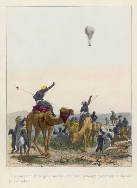 A balloonist is greeted by native Africans mounted on camels who wave toward this unusual sight