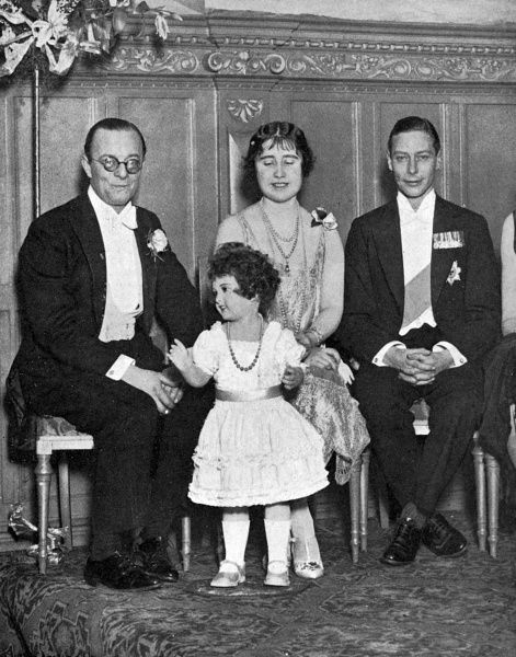 The Duke and Duchess of York and Mr Leslie Henson with a wax effigy of the young Princess Elizabeth. The doll was the piece de resistance of an auction held at a Society ball. Date: 1927