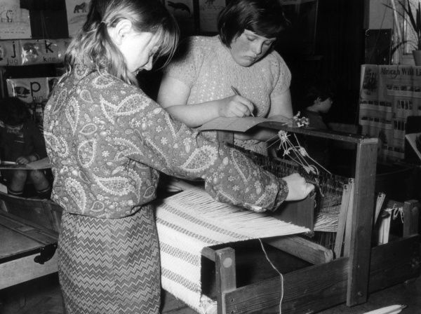 Schoolgirls learning to weave on a hand loom. Date: late 1960s