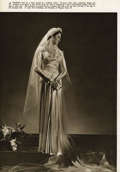Heavy white satin weddiing dress, exquisitely draped and moulded to the figure so that the line about the waist is emphasised, it has a heart-shaped neckline with fern clip at either side. The head-dress of pearly flowers is backed with tulle